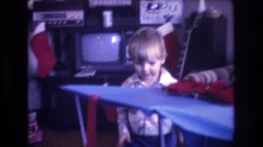 1975: a cute body is taking boxes of presents and throws on the table BAXTER Stock Footage