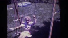 1976: two children swinging on swingset with glider seat swing  Stock Footage