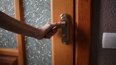 Woman hand opening wooden door. Holding a gold door handle Stock Footage