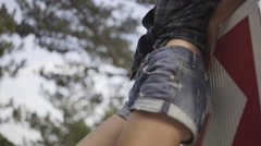 Hipster girl in denim shorts standing on the street Stock Footage
