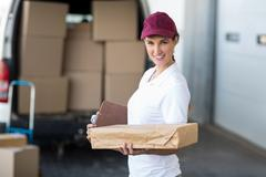 Portrait of delivery woman holding a clipboard and parcel Kuvituskuvat