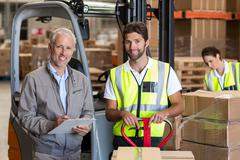 Portrait of warehouse manager and workers preparing a shipment Stock Photos