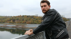 Man in black leather jackets looking at river Stock Footage