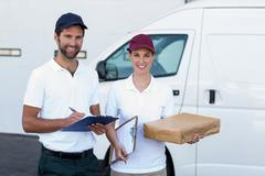 Portrait of delivery man and woman standing with clipboard and parcel Kuvituskuvat