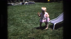 1976: baby playing on grass next to slide with man and dog  Stock Footage