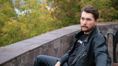 Brutal man in a leather jacket sitting on a park bench Stock Footage