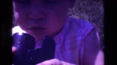 1976: a baby playing outside investigates a gadget MT BROMLEY VERMONT Stock Footage