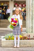 Grower Baby girl first-grader with a bouquet of flowers at the school Stock Photos