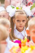 Thoughtful first grader in the crowd of classmates on line the first of Septe Stock Photos