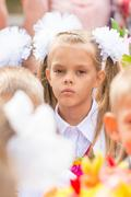 First grader tired of classmates in the crowd at the first line of September Stock Photos