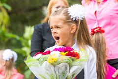 First grader with a bouquet of flowers yawns at school in a crowd Stock Photos
