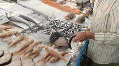 A fishmonger cuts up a fish at athens central market Stock Footage