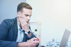 Good looking dissatisfied man having headache by working place Stock Photos