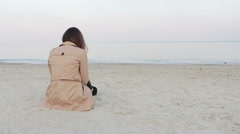 Woman in beige coat sitting on the beach Stock Footage