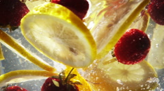 Slow Motion Whirlpool with Sliced Lemon and Strawberry Stock Footage