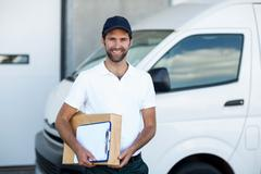 Portrait of delivery man holding parcels and clipboard Kuvituskuvat