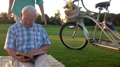 Elderly couple reading a book. Stock Footage
