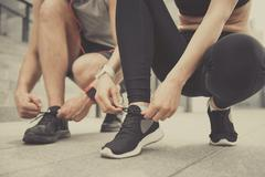 Active man and woman tying their shoelaces Stock Photos