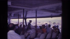 1977: a large group of people seated on a watercraft looking out Stock Footage