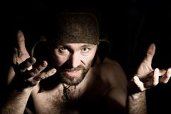 Dark portrait of scary evil sinister bearded man with smirk, makes various hand Stock Photos