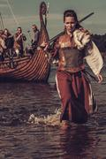 Confident viking woman with sword walking along the shore with Drakkar on the Stock Photos