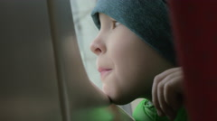 Close up view of small boy bored face in winter hat on his place in the rail Stock Footage