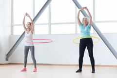 Persistent positive women exercising with hula hoops Kuvituskuvat