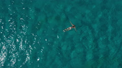 Aerial - Top down view of a woman swimming underwater in a deep blue water Stock Footage
