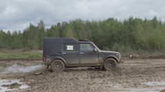Jeep rides on a dirt road. The car enters the puddle of mud Stock Footage