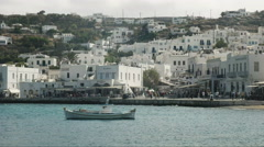 Panning shot of a fishing boat and the waterfront of chora, mykonos Stock Footage