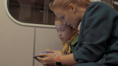 Shot of mother and son ride in the subway train using smartphone during trip Stock Footage
