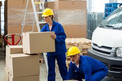 Delivery workers unloading cardboard boxes from pallet jack Stock Photos