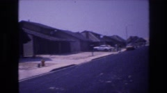 1977: tarmac road with houses with garages in a row and a few cars LAS VEGAS Stock Footage