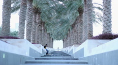 Boy running down the stairs with palm trees on the sides Stock Footage