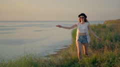 Young woman in walk dance and jump on the edge of a cliff enjoying the nature Stock Footage