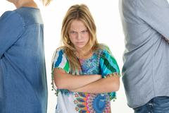 Sad girl standing between divorcing father and mother Stock Photos