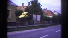 1967: a road runs through a scenic village with elegant houses on one side Stock Footage