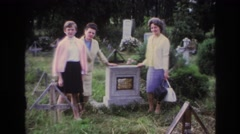 1967: two women and a girl stand next to a gravestone in a graveyard FRANCE Stock Footage