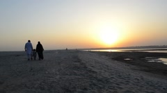 Muslim family with kid walking on sand during evening Stock Footage