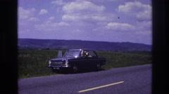 1967: car hills prairie flowers, waving, sunny clouds roadside highway FRANCE Stock Footage
