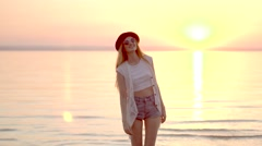 Pretty young blonde girl in hat posing on background of ocean and golden sunset Stock Footage