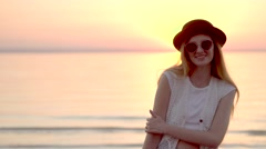 Pretty young girl in hat and sunglasses posing on background of golden sunset Stock Footage