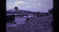 1967: people walk through the stony pavement on the shore of a small lake FRANCE Stock Footage