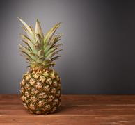 Raw whole pineapple on wooden surface table Stock Photos