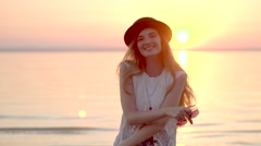 Pretty blonde woman in hat enjoying summer vacation on the ocean golden sunset Stock Footage