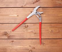 Metal plumber wrench with red handles on wooden surface Stock Photos