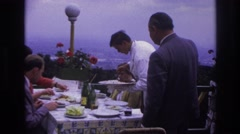 1967: butler serving mashed potatoes onto one of the plates of the people  Stock Footage