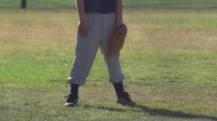 A boy playing short stop in a little league baseball game, slow motion. Stock Footage