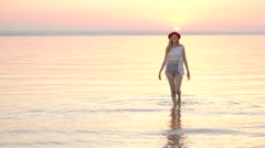 Young blonde woman in hat enjoying summer holidays on the ocean golden sunset Stock Footage