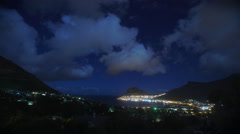 Night time lapse of clouds rolling over coastal village Stock Footage